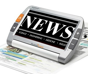 "The image shows the Explore 7 on a white background. It is magnifying a magazine page it is resting on, and the word 'NEWS"" is seen on the screen in white writing on a black background."