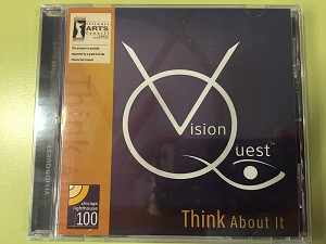 The image shows a CD. It has a purple cover with a yellow stripe running down the left side. The words Vision Quest  and Think About It are printed on the front of the CD.
